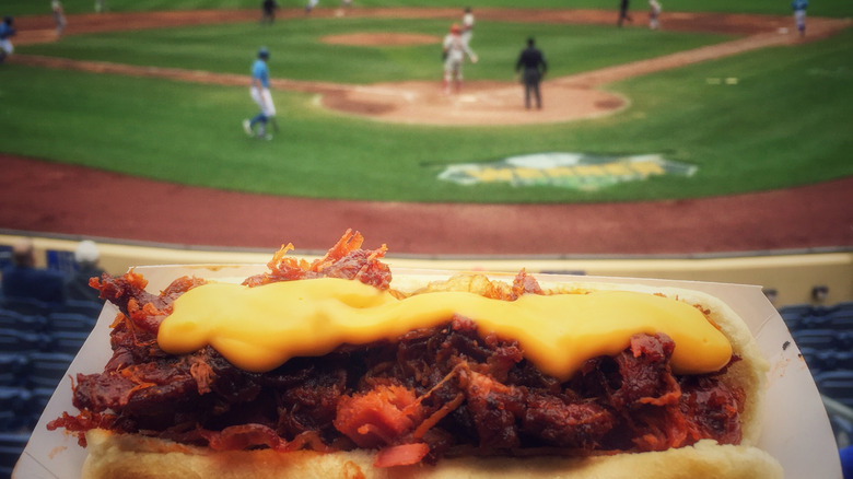 Chili cheese hot dog with view of ballpark in background