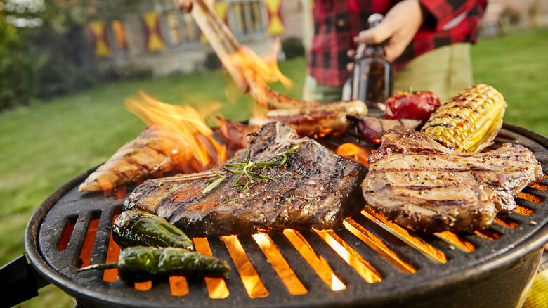 A person grilling meat outdoors