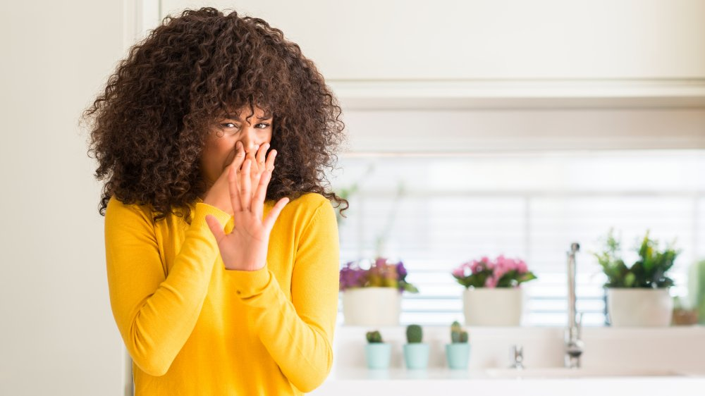 Women smelling something bad in a kitchen