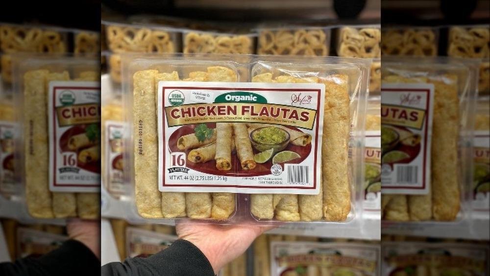 hand holding chicken flautas
