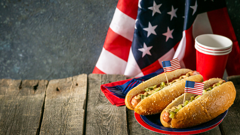 Two hot dogs with paper cups and an American flag