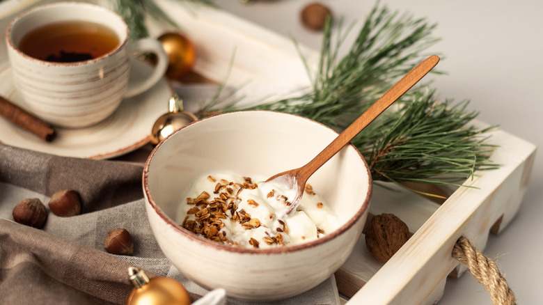 Bowl of Greek yogurt with granola on tray with tea, nuts, spices, and holiday décor