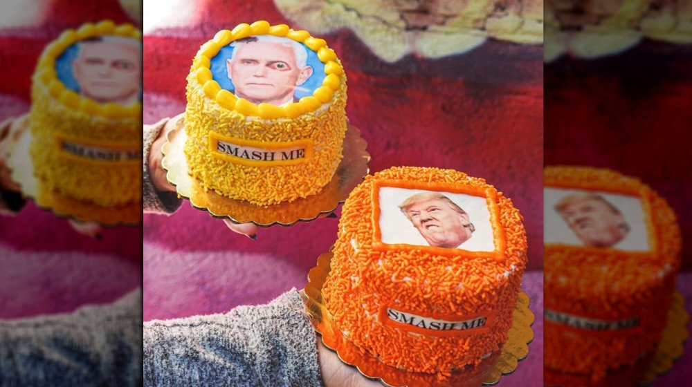 """Colorful cakes topped with images of Pence and Trump, with words """"smash me"""" written on side"""