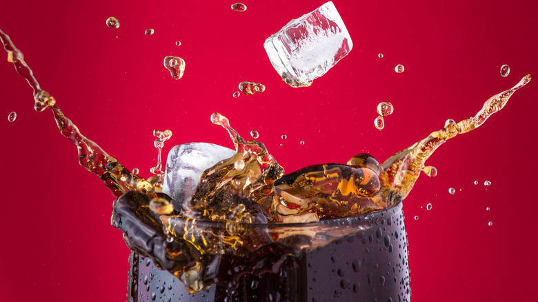 Glass of Coca-Cola with ice splashing out against red background
