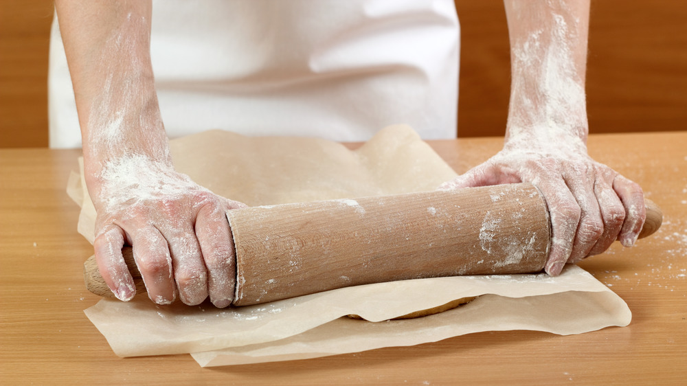 Baker rolling out dough