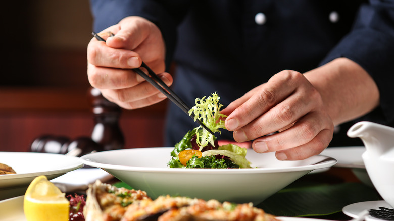 A person finely arranges a salad on a white plate