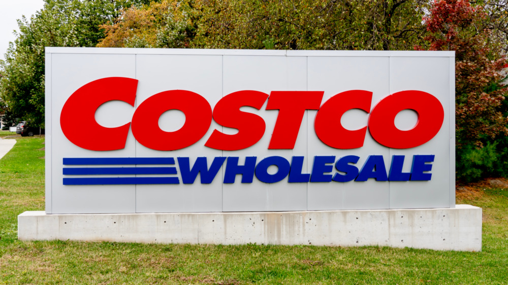 A Costco sign and greenery