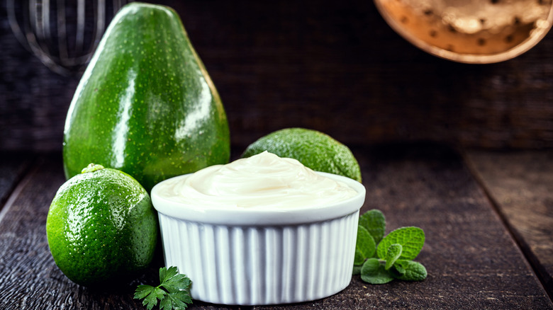 A dish of mayonnaise in front of an avocado