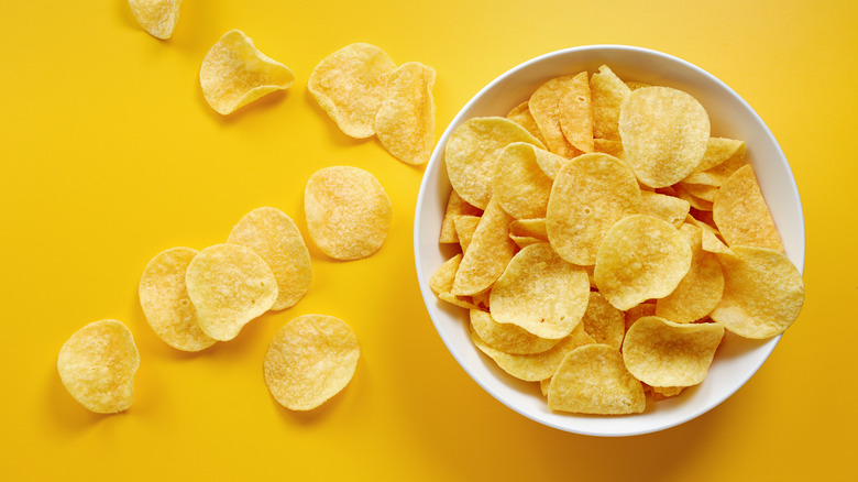 Potato chips in white bowl against yellow background