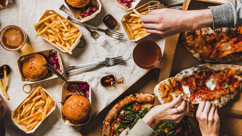 Hands reaching for an array of foods