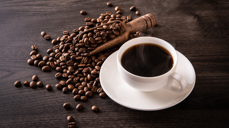 cup of black coffee next to coffee beans