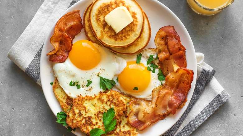 Fried eggs, silver dollar pancakes, bacon, and hash browns on a plate