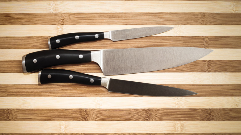 three knives on a wooden cutting board