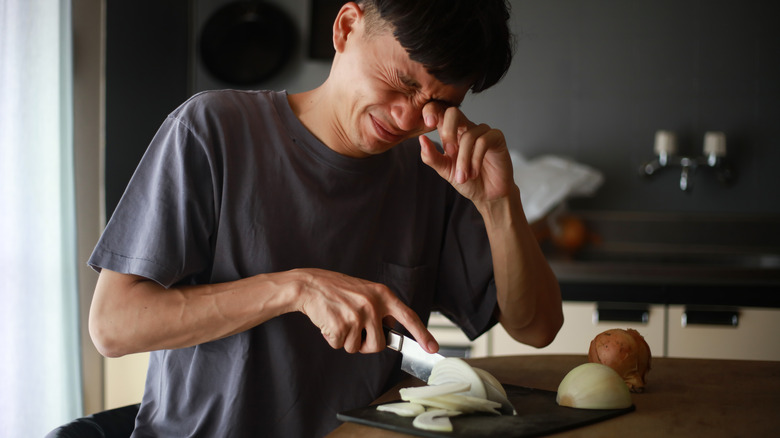 A man crying while chopping onions