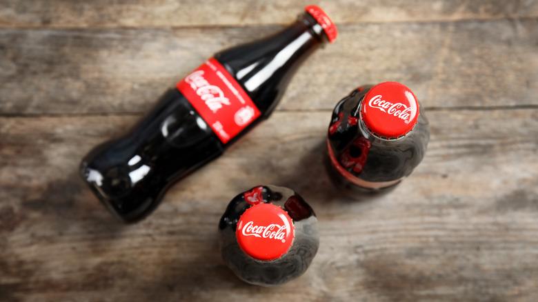Coke bottles against wooden background