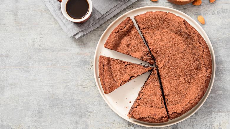 Cut flourless chocolate cake next to cup of espresso