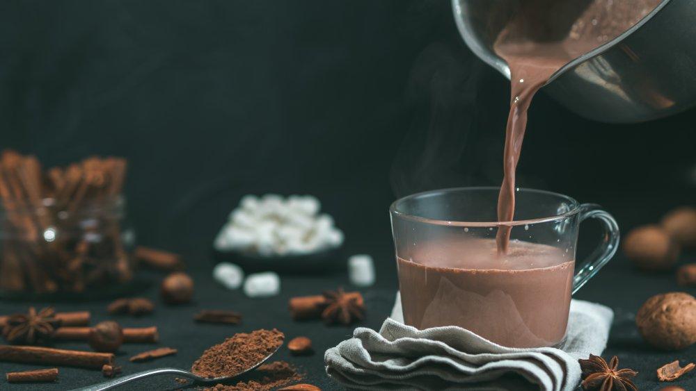 pouring hot cocoa into a glass mug