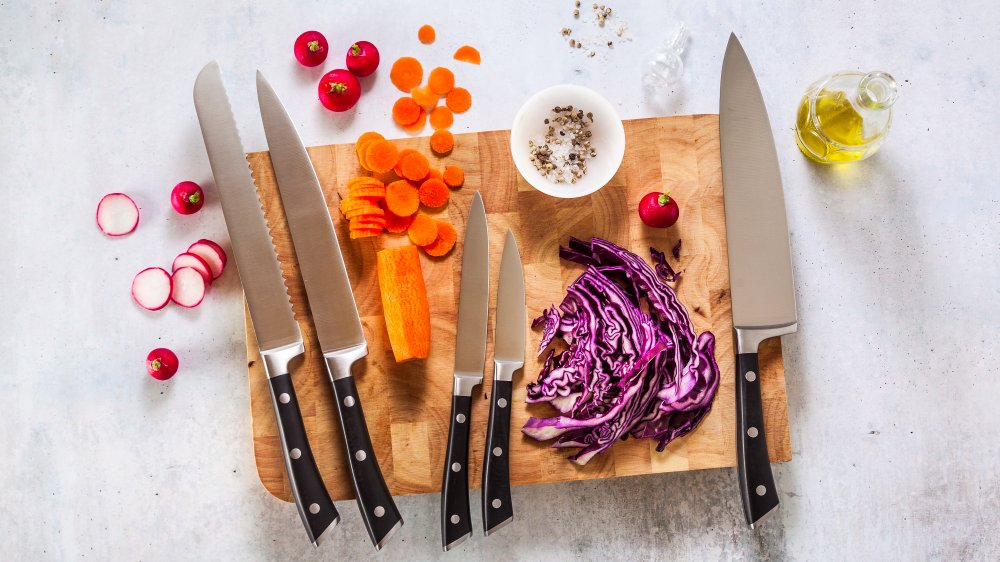 kitchen knives on a cutting board with diced vegetables