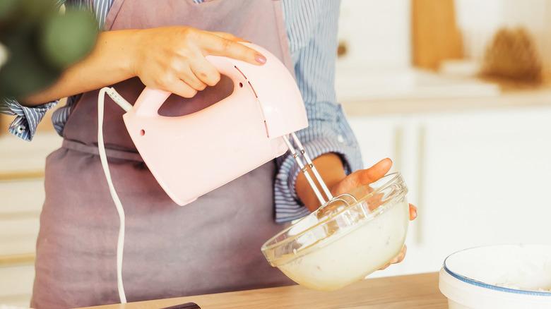 Woman using electric mixer