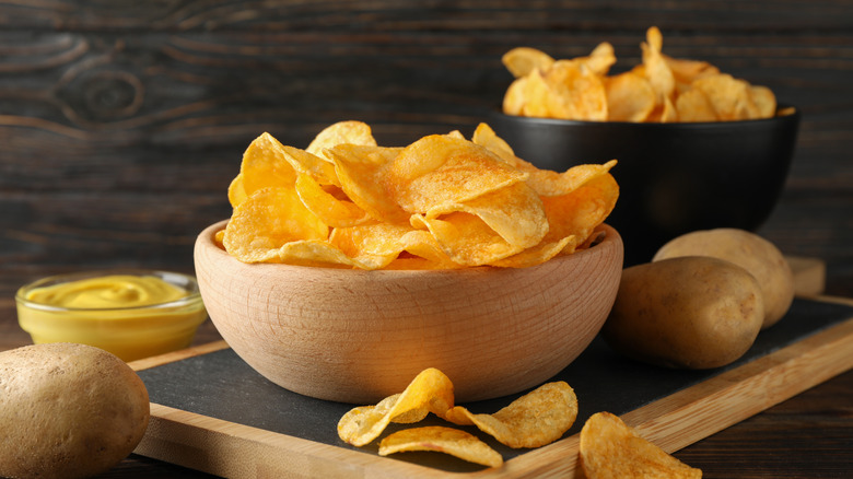 Potato chips and mustard dip on wood table