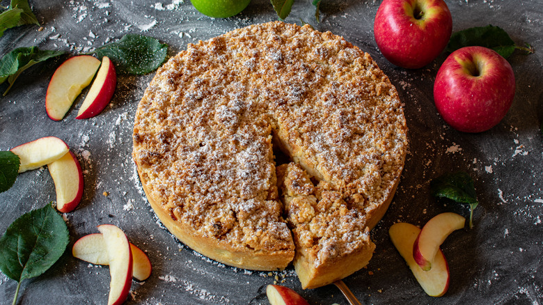 Apple crumb cake with piece cut out on marble slab
