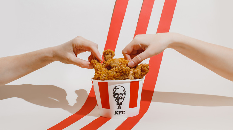 KFC chicken in a bucket with two hands taking pieces