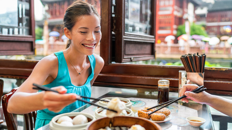 Woman eating in Chinese restaurant