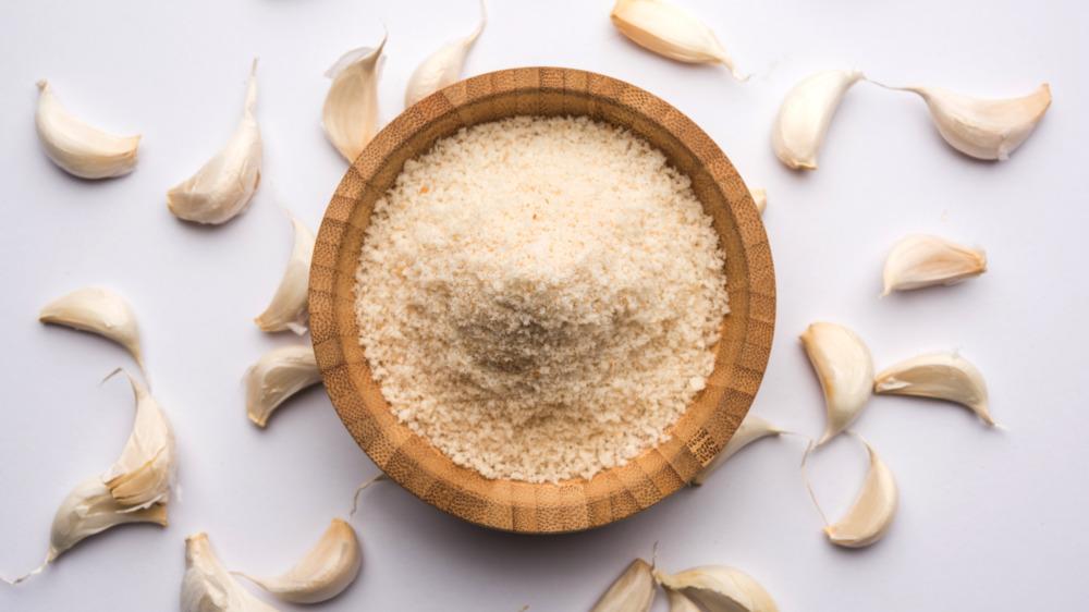 Bowl of garlic powder with garlic bulbs