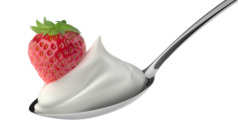 A spoonful of whipped cream with a strawberry.