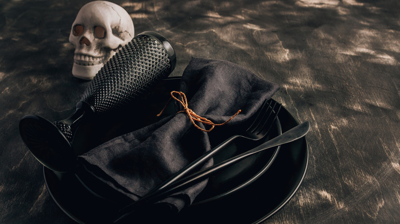 All black table setting next to skull