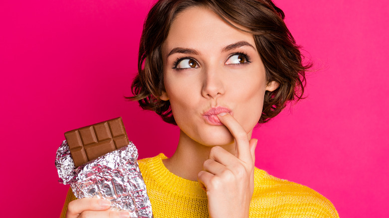 Woman licking chocolate off finger