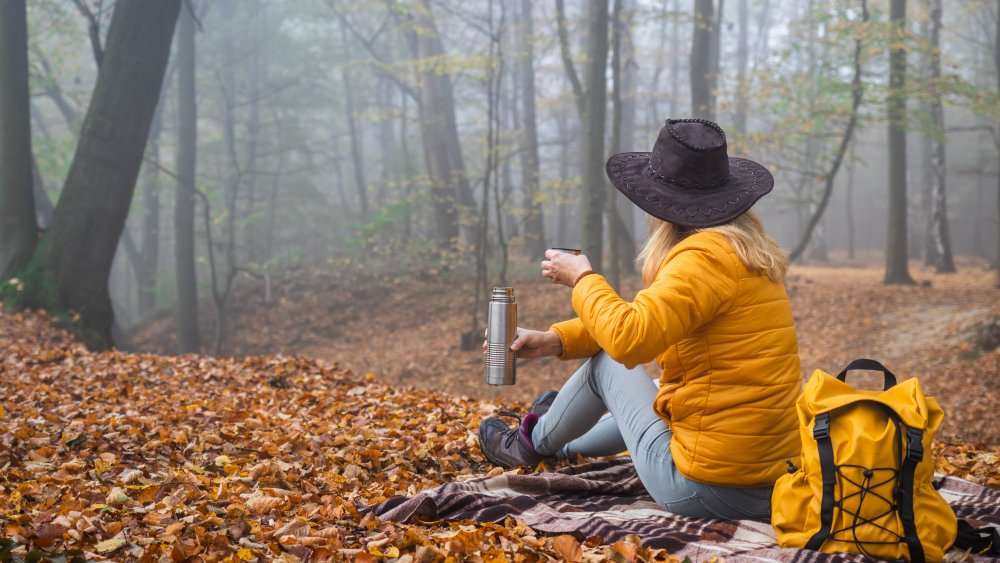woman drinking coffee while camping in woods