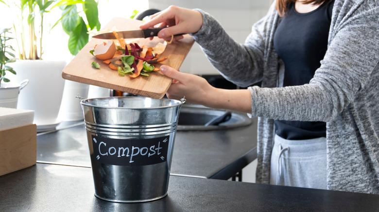 Putting food scraps in compost bucket