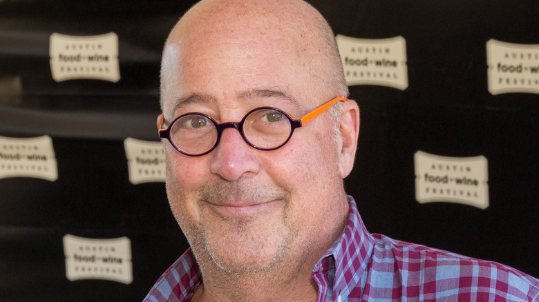 Andrew Zimmern wearing glasses and plaid shirt
