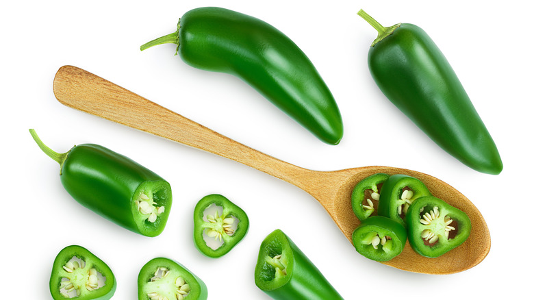 Whole and cut up jalapenos with wooden spoon