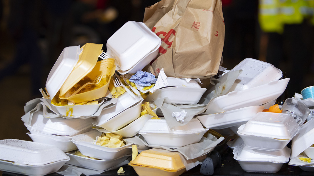 Discarded food containers cluttering a trash can