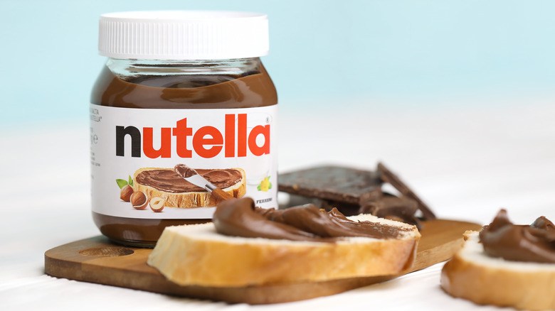 Jar of Nutella with bread covered in Nutella