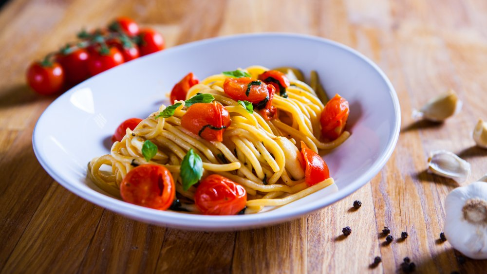 bowl of pasta with tomatoes and basil