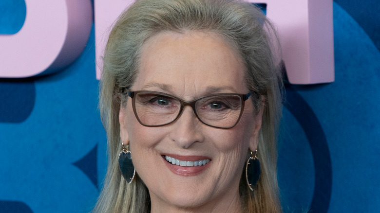 Meryl Streep smiles with glasses and heart earrings