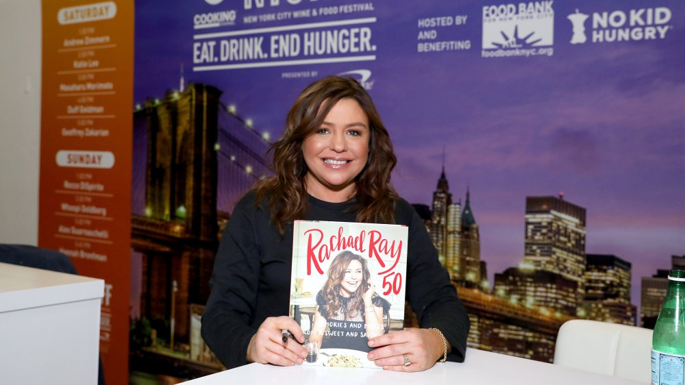 Rachael Ray holding up her cookbook