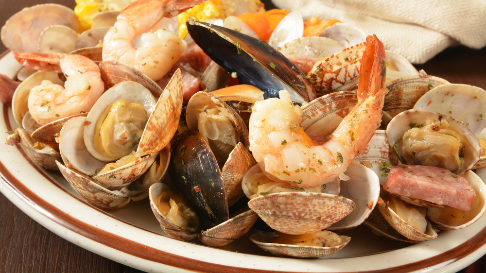 Closeup of New England style clambake with shrimp mussels, clams and sausage on white plate