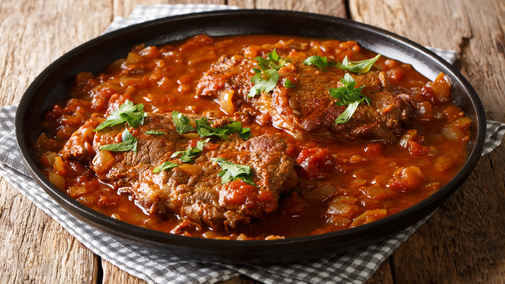 Swiss steak, smothered steak, cubed steak in a skillet with tomato gravy, tomato sauce