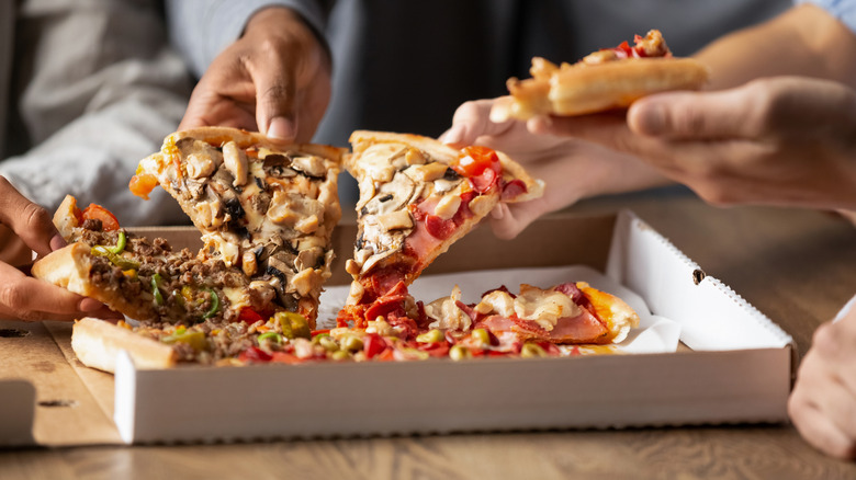 Hands reaching into pizza box grabbing slices of pizza