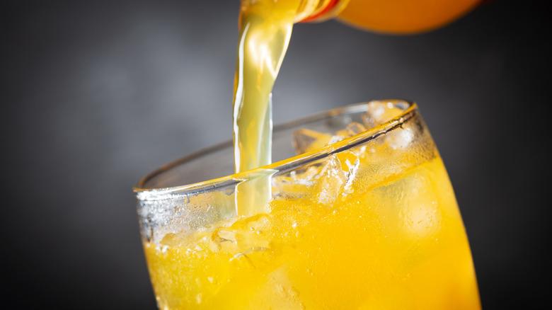 orange soda being poured into glass