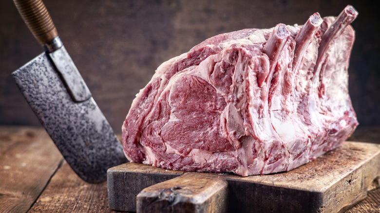 Raw standing rib roast and cleaver