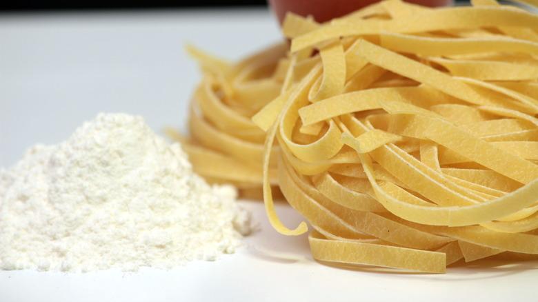 Ground white flour next to pasta noodles