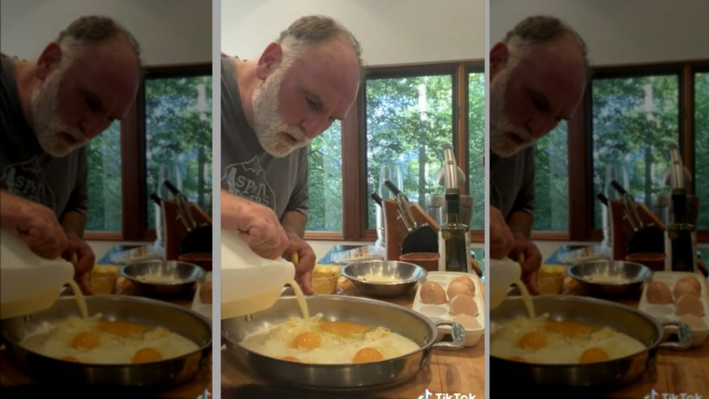 Jose Andres making eggs, pouring milk into pan.