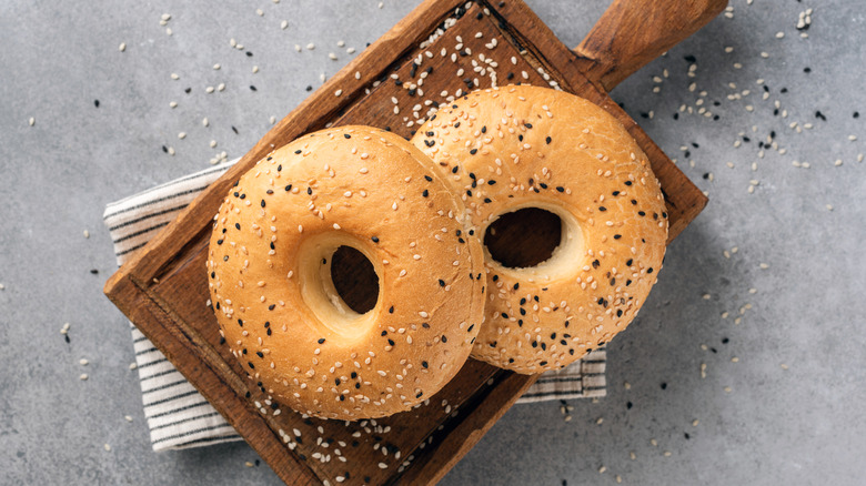 Two bagels on a wooden cutting board