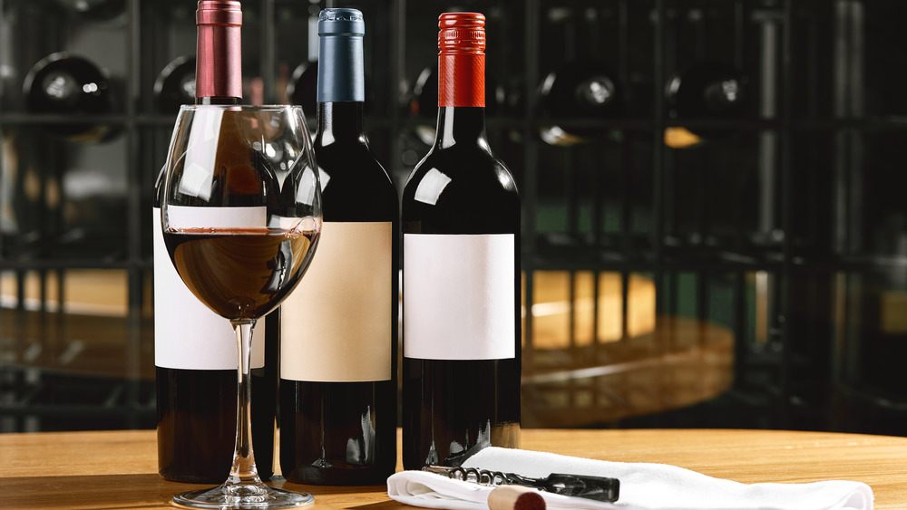 Glass of red wine in front of three bottles