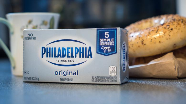 A block of Philadelphia cream cheese next to bagel